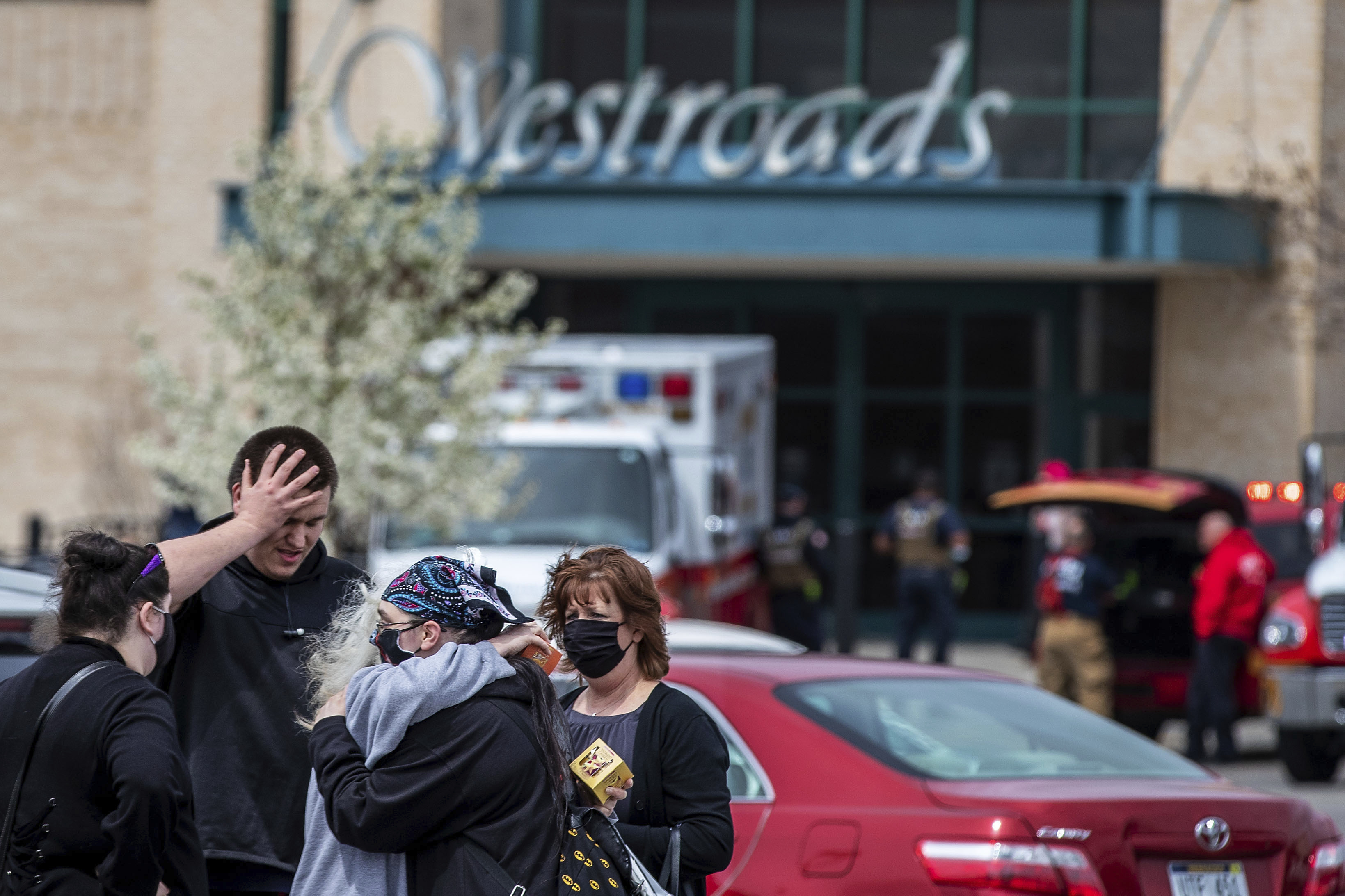 People hug in the parking lot after a shooting at Westroads Mall in Omaha, Nebraska, on April 17, 2021.
