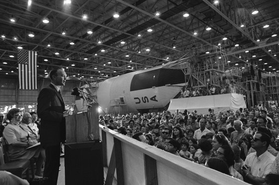 Astronaut Michael Collins addresses a crowd at the New Orleans Michoud Assembly Plant as a model of the giant Saturn 5 booster that sent the Apollo crew on their way to the moon rests in the background on Sept. 6, 1969.