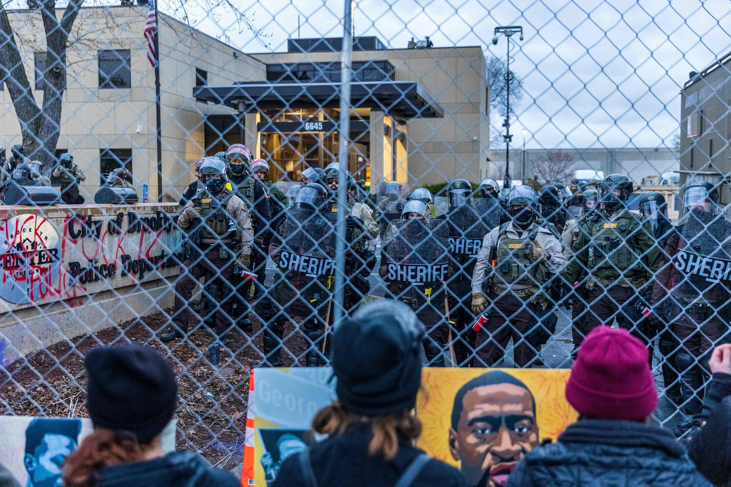 Sheriff officers stand guard outside the Brooklyn Center police station as demonstrators stand on the other side of the chain-link fence protesting the death of Daunte Wright who was shot and killed by a police officer in Brooklyn Center, Minn. on April 14, 2021.