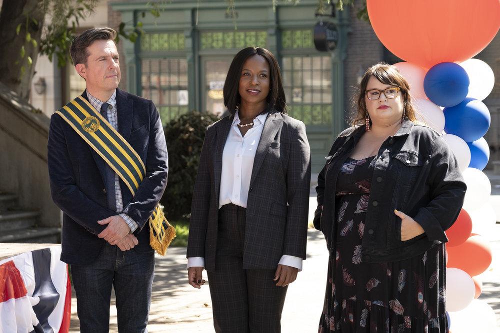 Pictured: (l-r) Ed Helms as Nathan Rutherford, Dana L. Wilson as Mayor Deirdre, Jana Schmieding as Reagan Wells