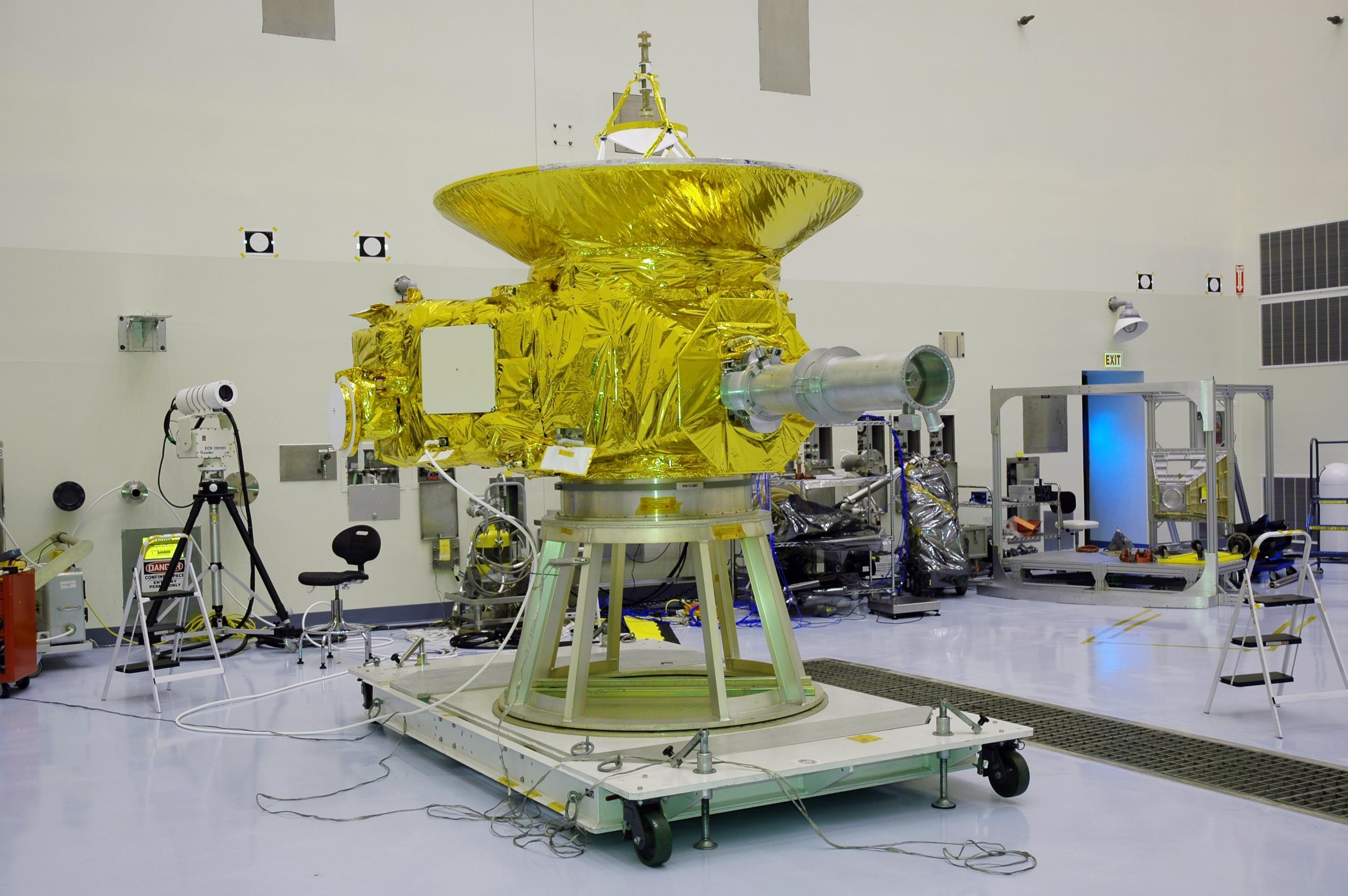In NASA Kennedy Space Center's Payload Hazardous Servicing Facility, the New Horizons spacecraft sits on a work stand before its launch