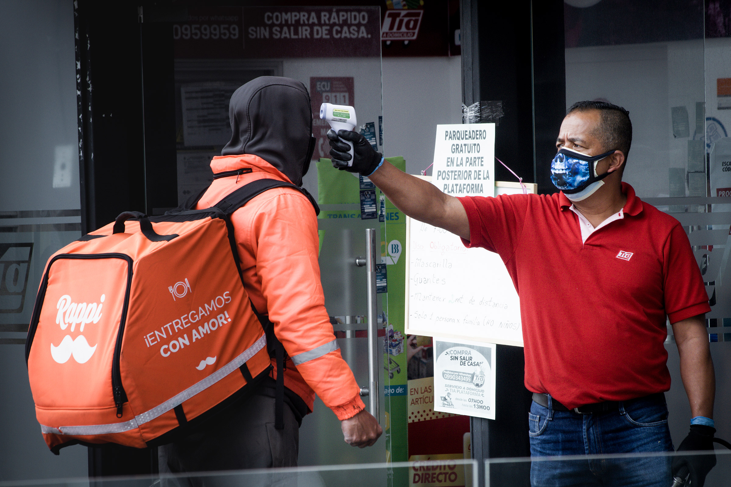 A guard at a store checks the temperature of a delivery driver in Quito, Ecuador, during the government lockdown to prevent the spread of COVID-19.