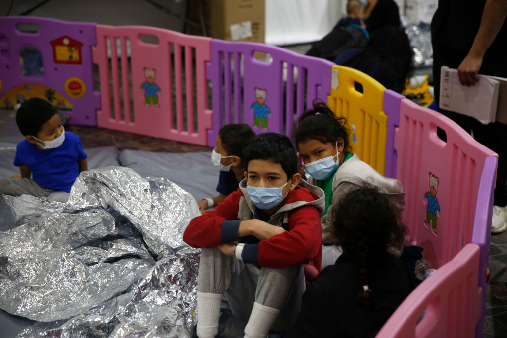 Young unaccompanied migrant children, ages 3-9 sit inside a play pen in the Department of Homeland Security holding facility on March 30, 2021 in Donna, Texas.