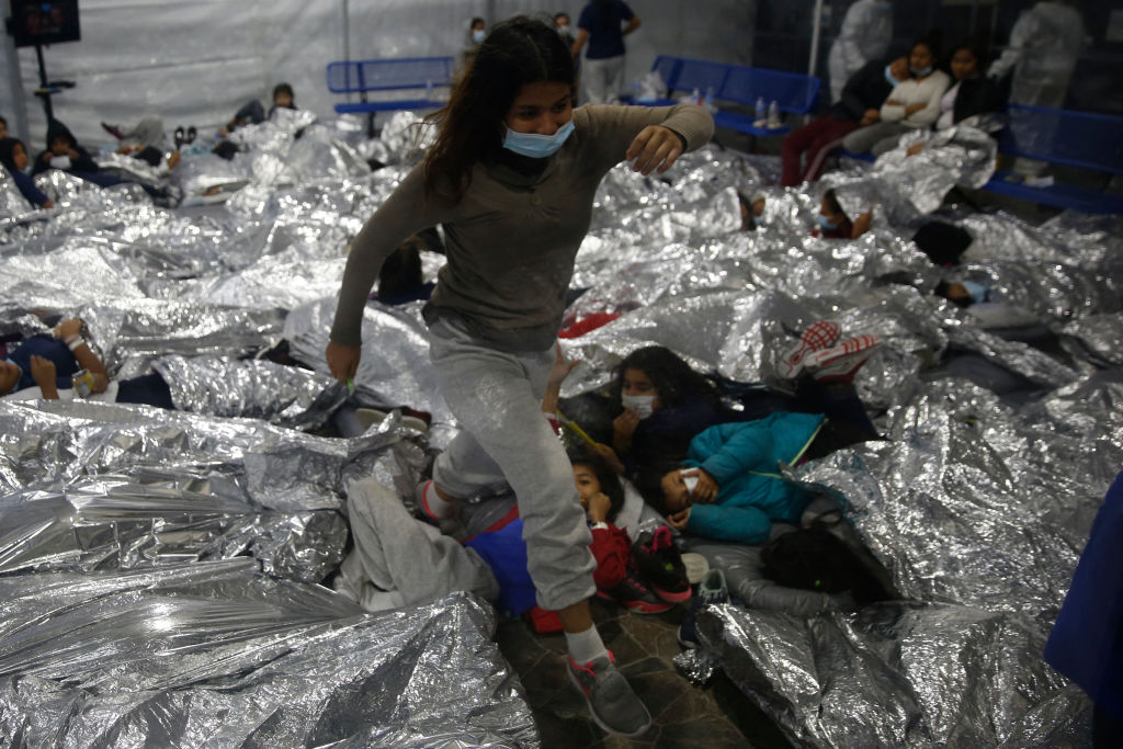 A young girl walks over others as they lie inside a pod for females at the Department of Homeland Security holding facility in Donna, Texas.