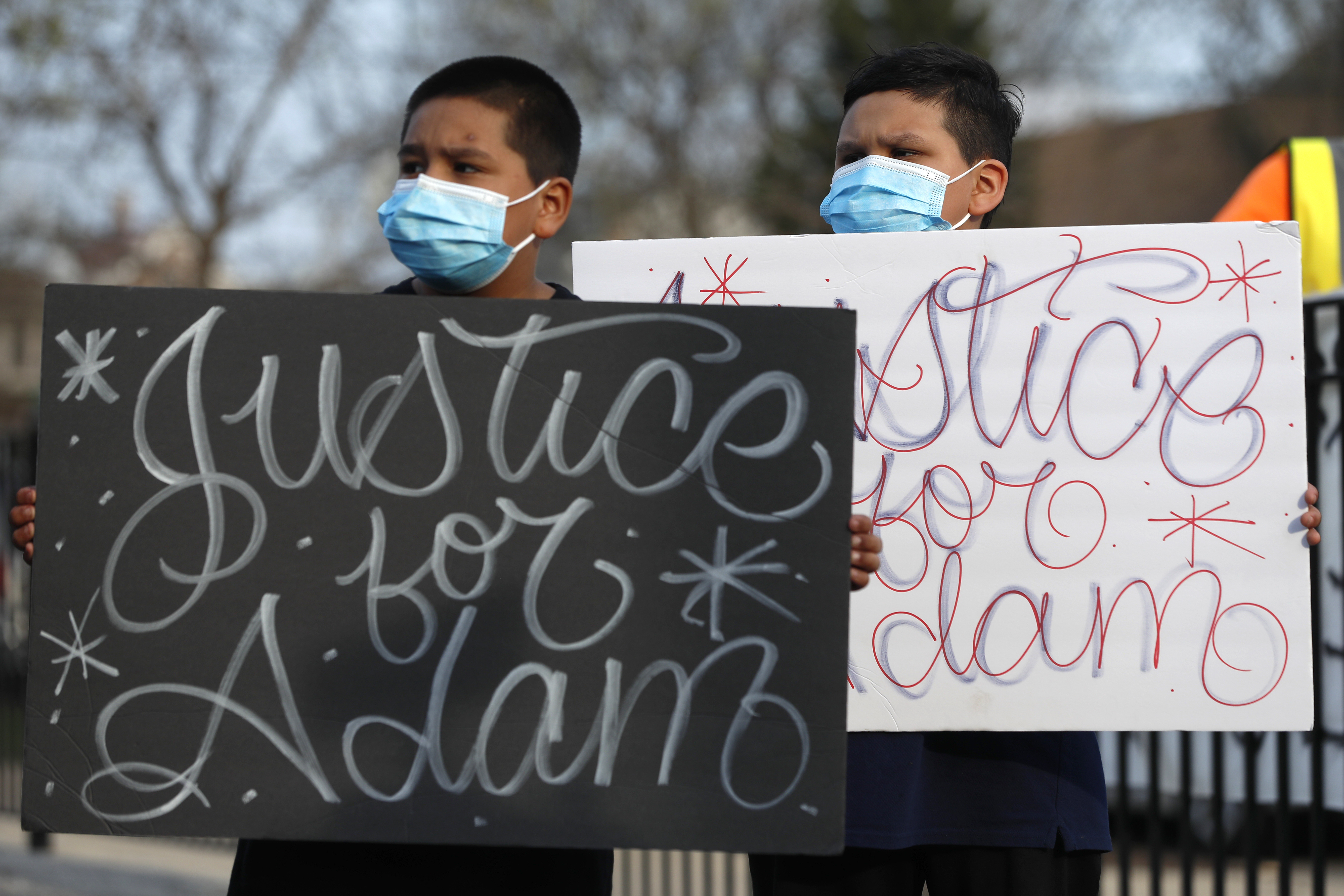 In this April 6, 2021 Jacob Perea, 7, left and Juan Perea, 9, hold signs as they attend a news conference following the death of 13-year-old Adam Toledo, who was shot by a Chicago police officer on March 29.