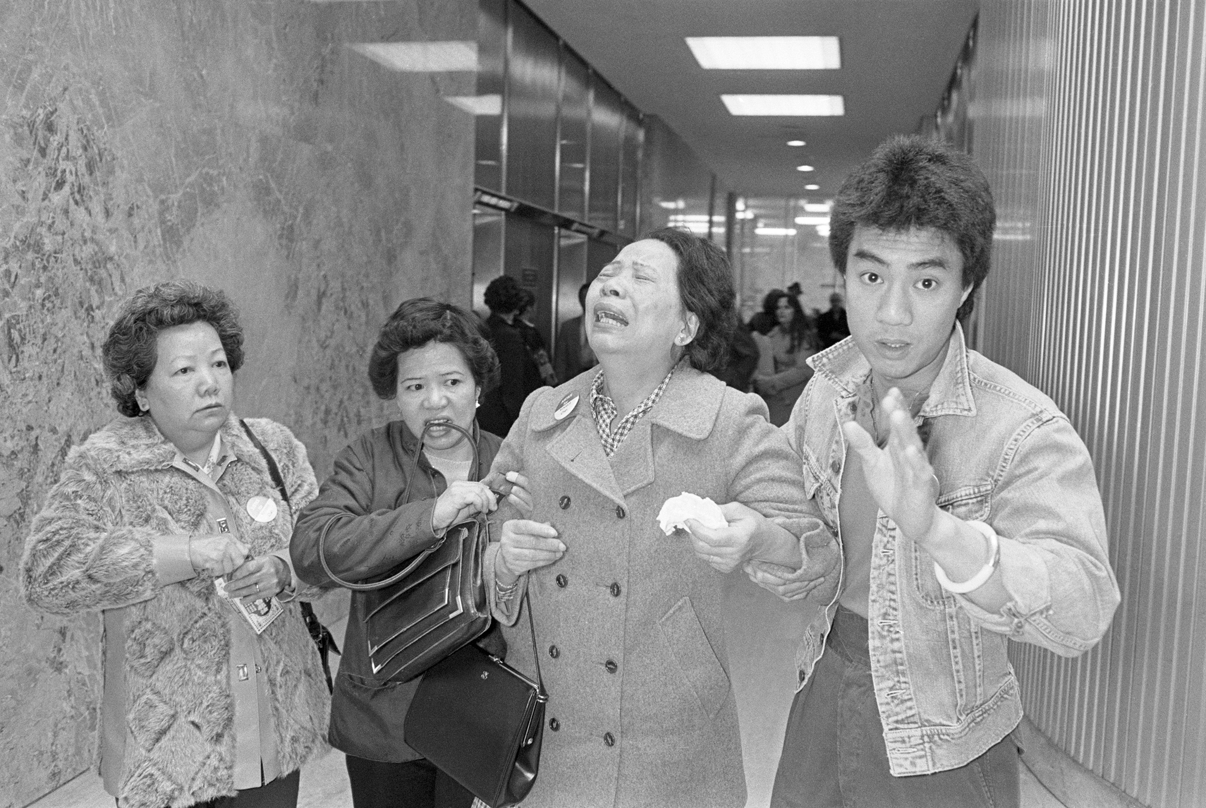 Lillie Chin, mother of Vincent Chin, who was clubbed to death by two white men in June 1982, breaks down as a relative (L), helps her walk while leaving Detroit's City County Building.