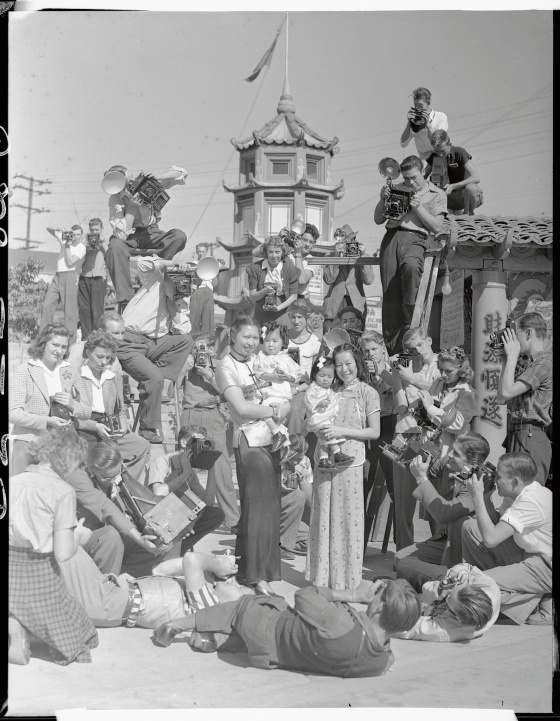 A mob of photographers descended upon China City, Los Angeles, when they heard that a prize contest is under way for the best amateur snaps of its people and its colorful nooks and corners. Pictured is a mob of candid camera fans shooting Mrs. Dorothy Siu (CQ) and Mrs. Chung Dat Loo as they hold little Gwendolyn Loo and Evelyn Loo on Oct. 1939