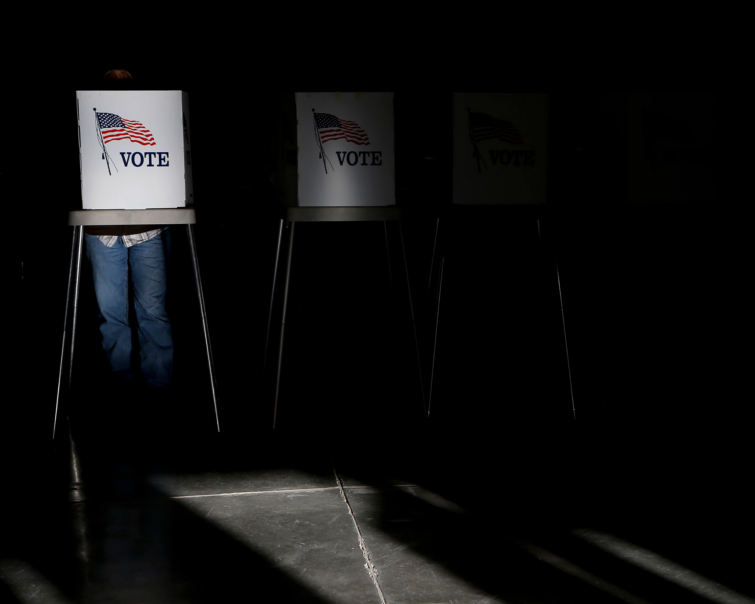 Voting booths are illuminated by sunlight as voters cast their ballots at a polling place.