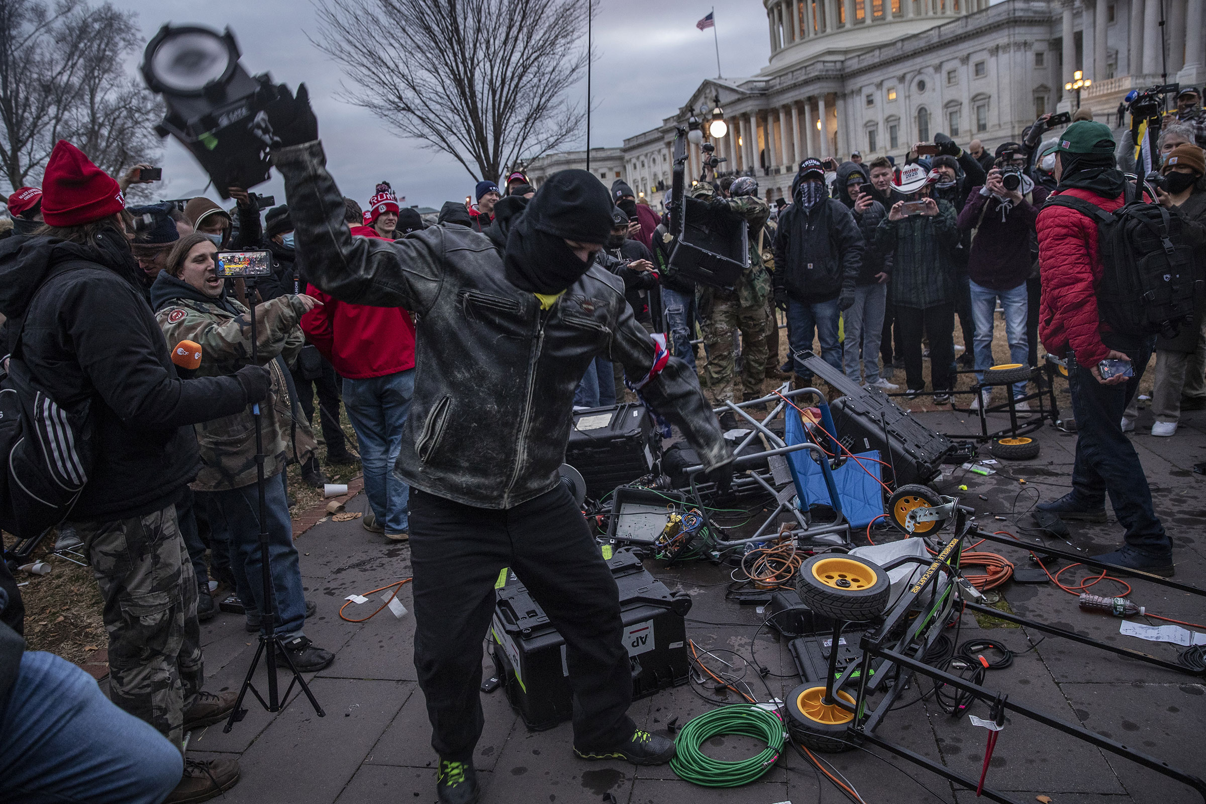 Demonstrators destroy broadcast video equipment outside the U.S. Capitol building after they earlier stormed the building in Washington, DC, U.S., on Wednesday, Jan. 6, 2021.