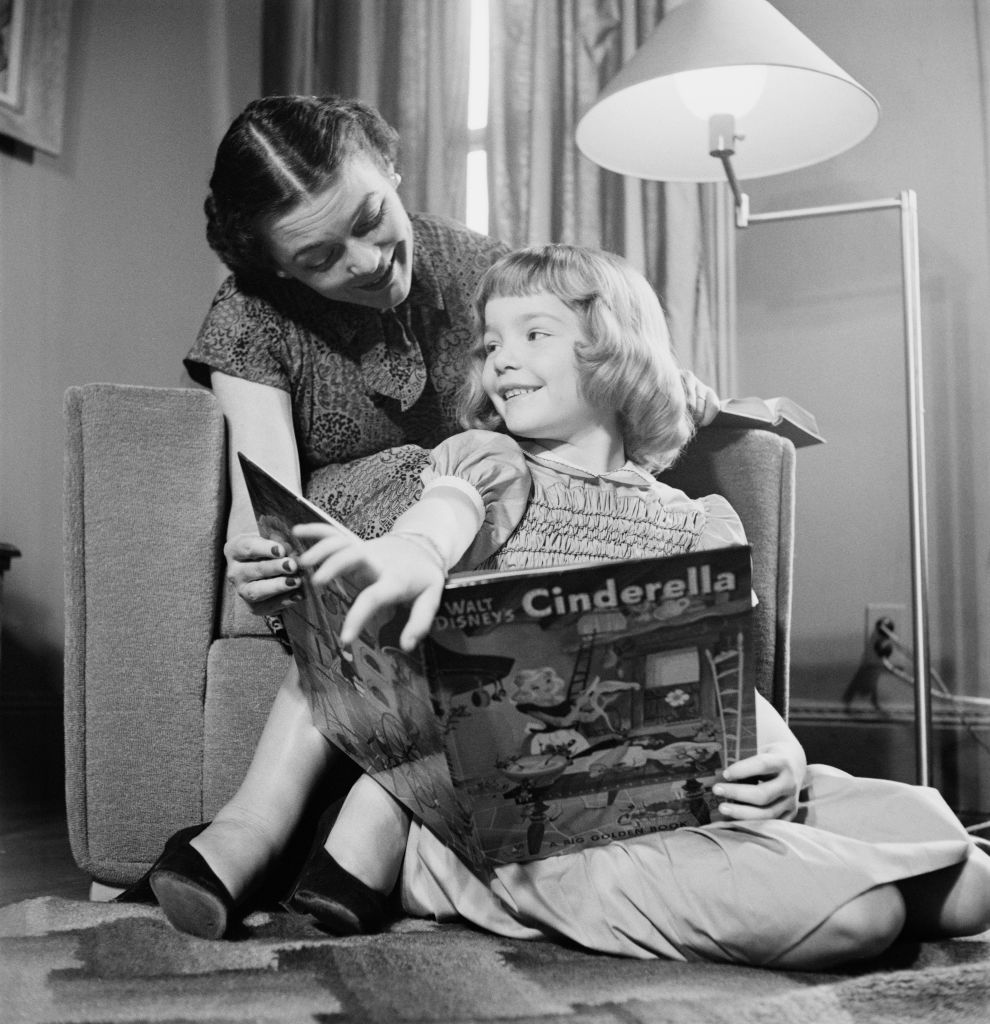 A little girl reading a 'Cinderella' book, circa 1950