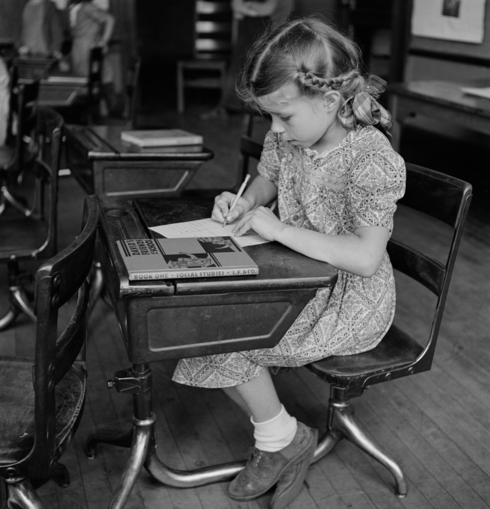 A girl in class with her social studies book. Southington, Conn., May 1942.