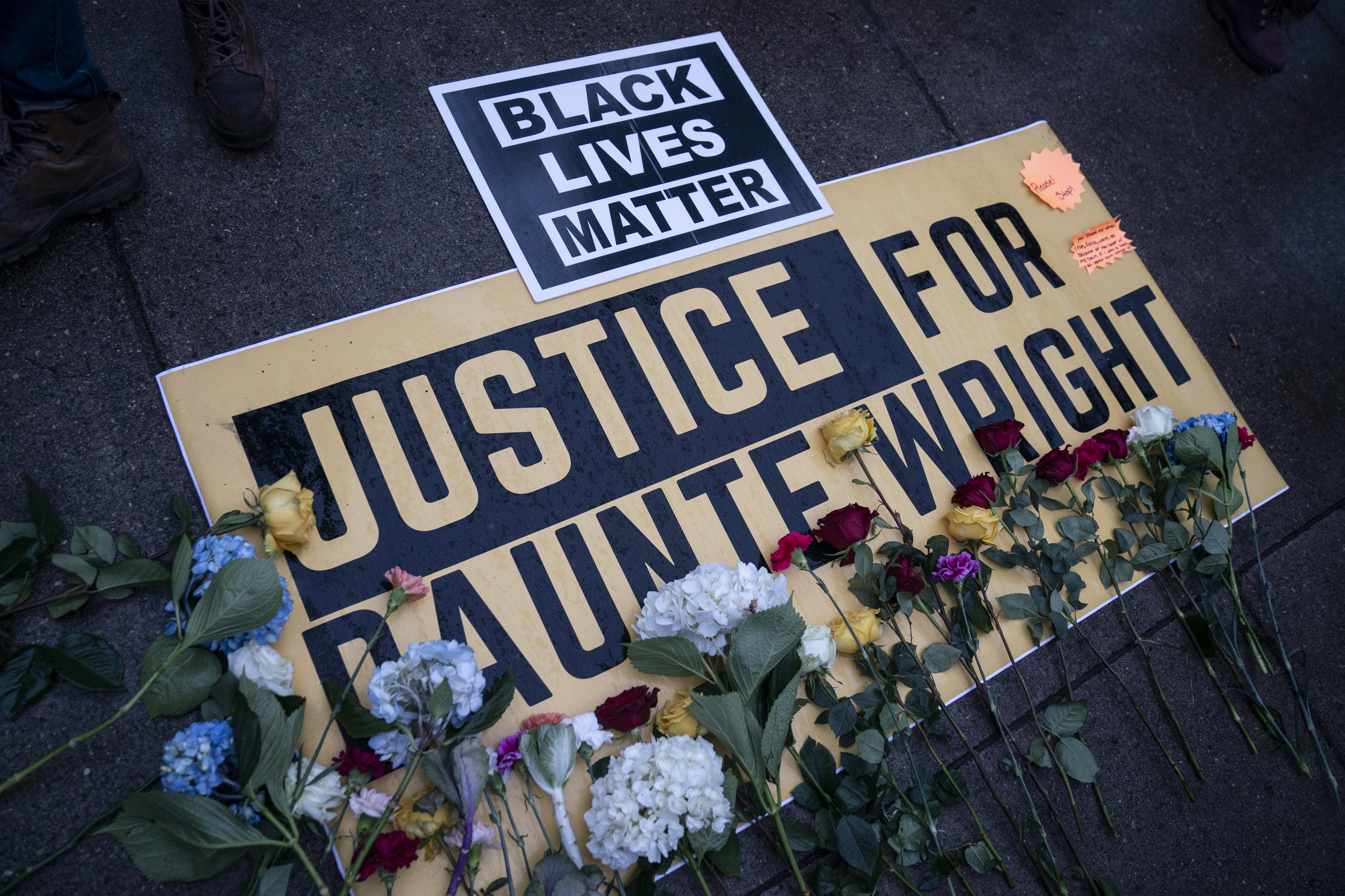 Flowers have been placed on a banner as demonstrators gather outside the Brooklyn Center Police Department on April 13, 2021 in Brooklyn Center, Minn., to protest Sunday's fatal shooting of Daunte Wright during a traffic stop.