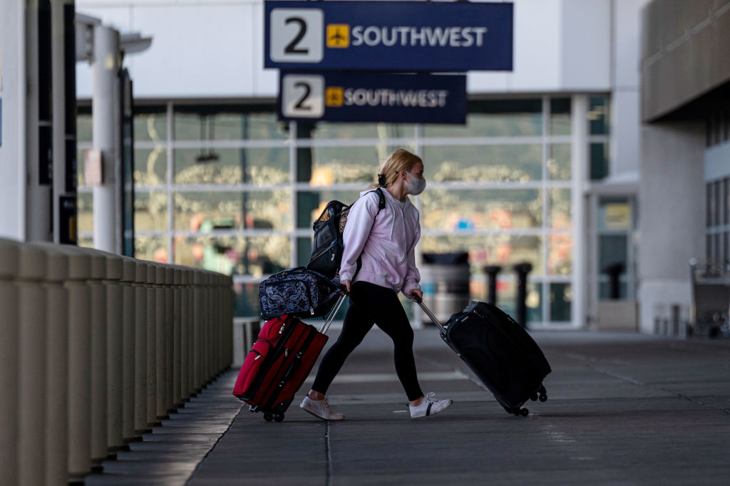 A traveler wearing a protective mask walks to the Southwest Airlines check-in area at Oakland International Airport in Oakland, California, U.S., on Tuesday, Jan. 19, 2021.