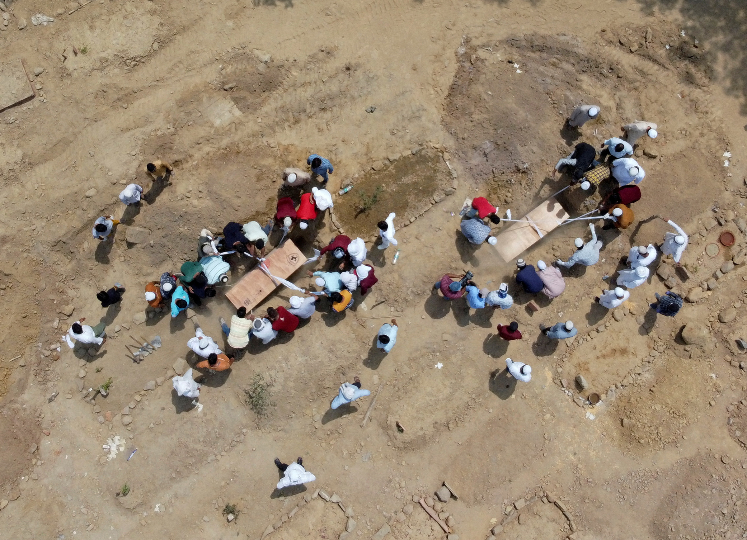 People bury the bodies of COVID-19 victims at a graveyard in New Delhi on April 16, 2021.