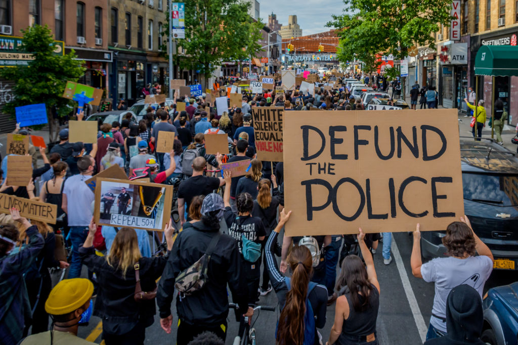 A participant holding a Defund The Police sign at a protest on June 2, 2020, in Brooklyn, N.Y.
