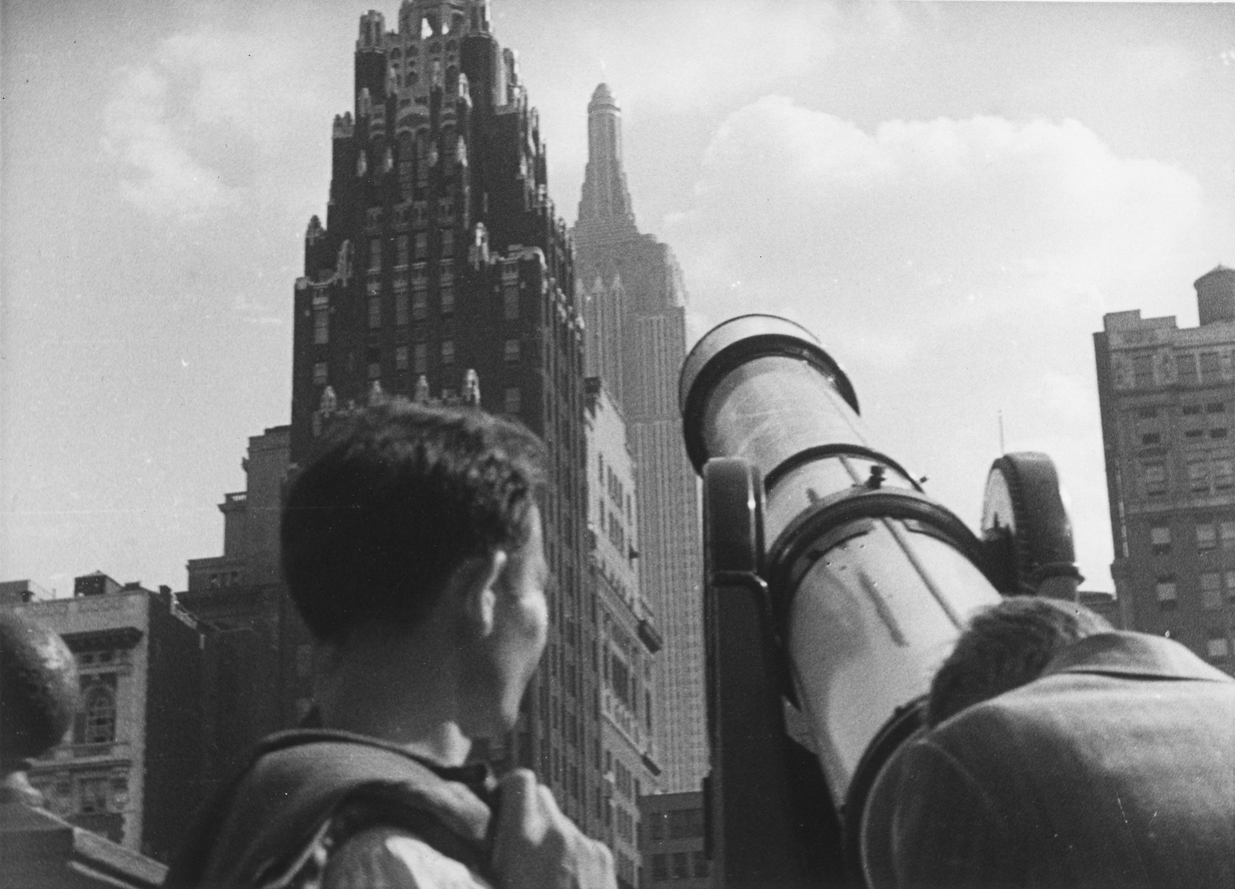 Tourists at Bryant Park looking through a telescope toward American Radiator Building and the  Empire State Building, New York City, circa 1930s.