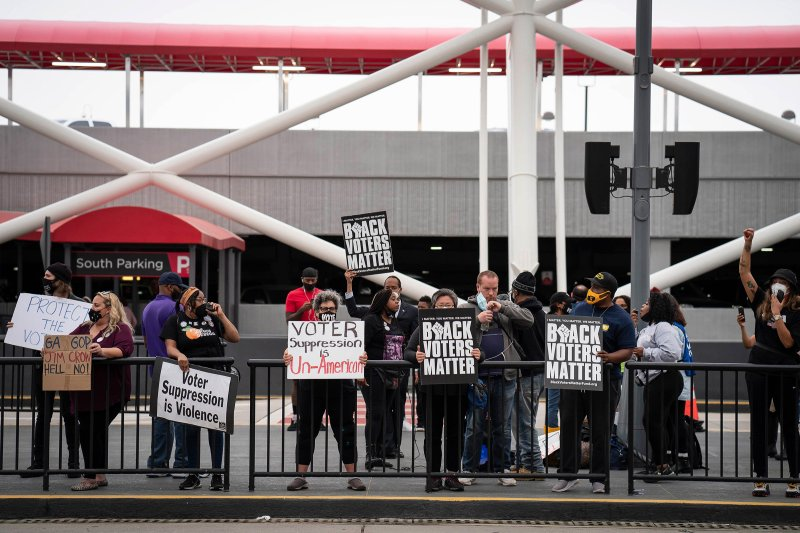 Voting-rights activists call for a boycott of Delta Air Lines during a protest at Hartsfield-Jackson Atlanta International Airport in Atlanta, March 25, 2021.