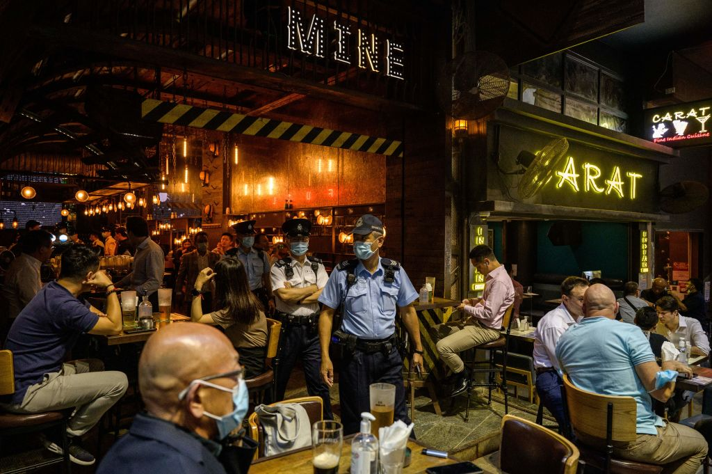 Food and Environmental Hygiene Department officers and police leave after inspecting the license of a restaurant and bar after it reopened, in Lan Kwai Fong, a popular drinking area in Hong Kong on April 29, 2021.