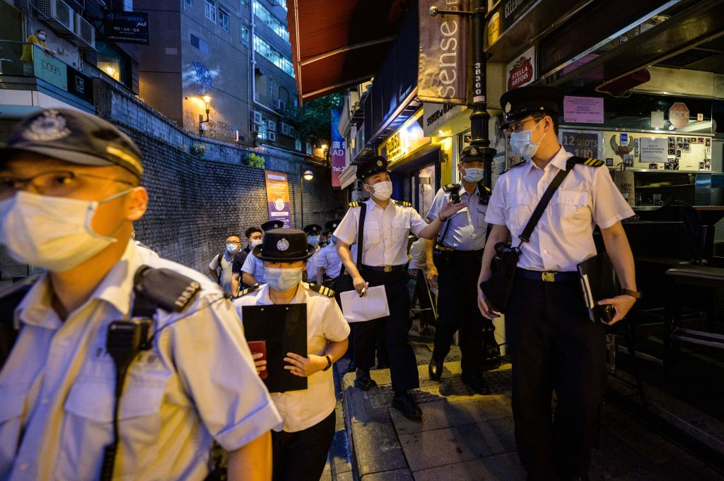 Food and Environmental Hygiene Department officers and police walk past restaurants and bars after they reopened, in Lan Kwai Fong, a popular drinking area in Hong Kong on April 29, 2021.