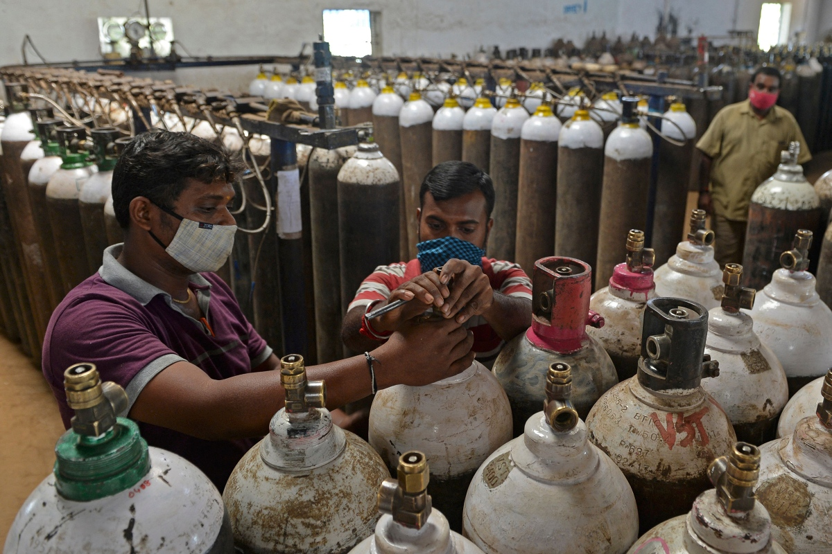 At a facility on the outskirts of Chennai on April 24, workers check medical oxygen cylinders that will be transported to hospitals.