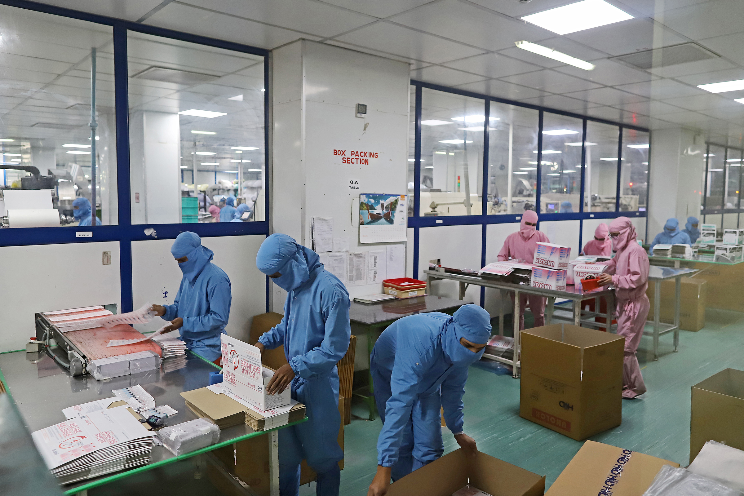 Employees pack boxes of syringes on the production line at the Hindustan Syringes and Medical Devices Ltd. facility in Faridabad, Haryana, on March 11.