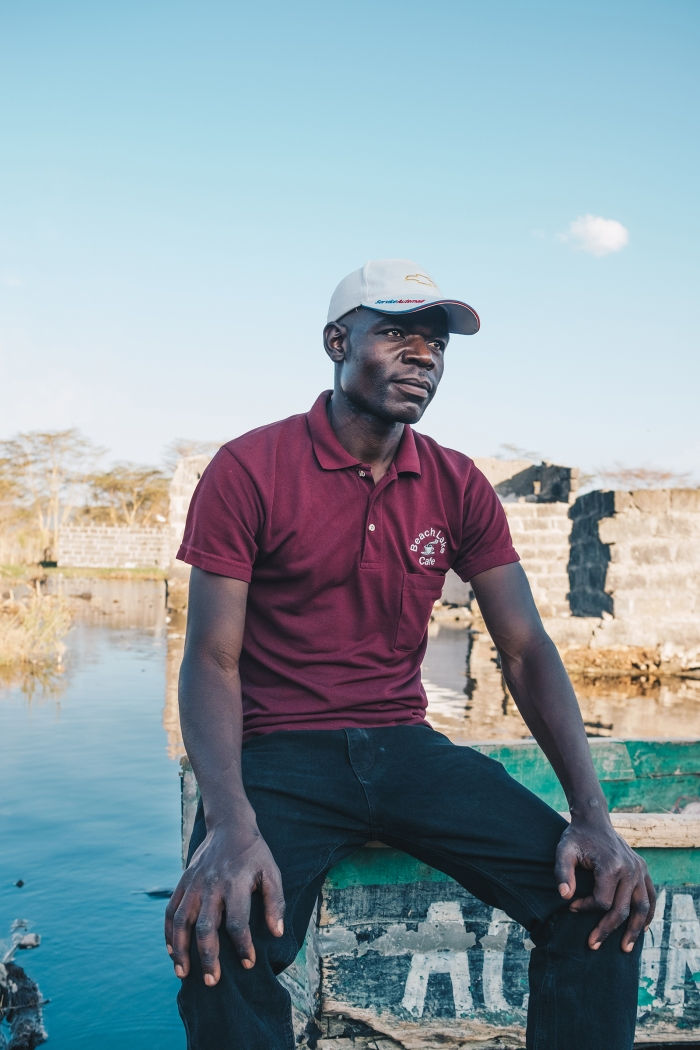 Gerrard Otieno sits on a boat in what used to be his living room in November. He is among hundreds of people displaced by Lake Nakuru's rising waters.