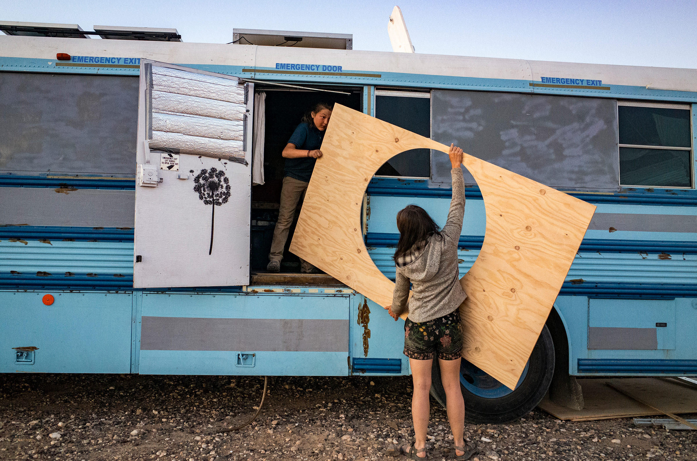 Paula and Max carry in a piece of wood to mount around Max's  hobbit bed  on the school bus, outside Ehrenberg, Az., on Feb. 8.