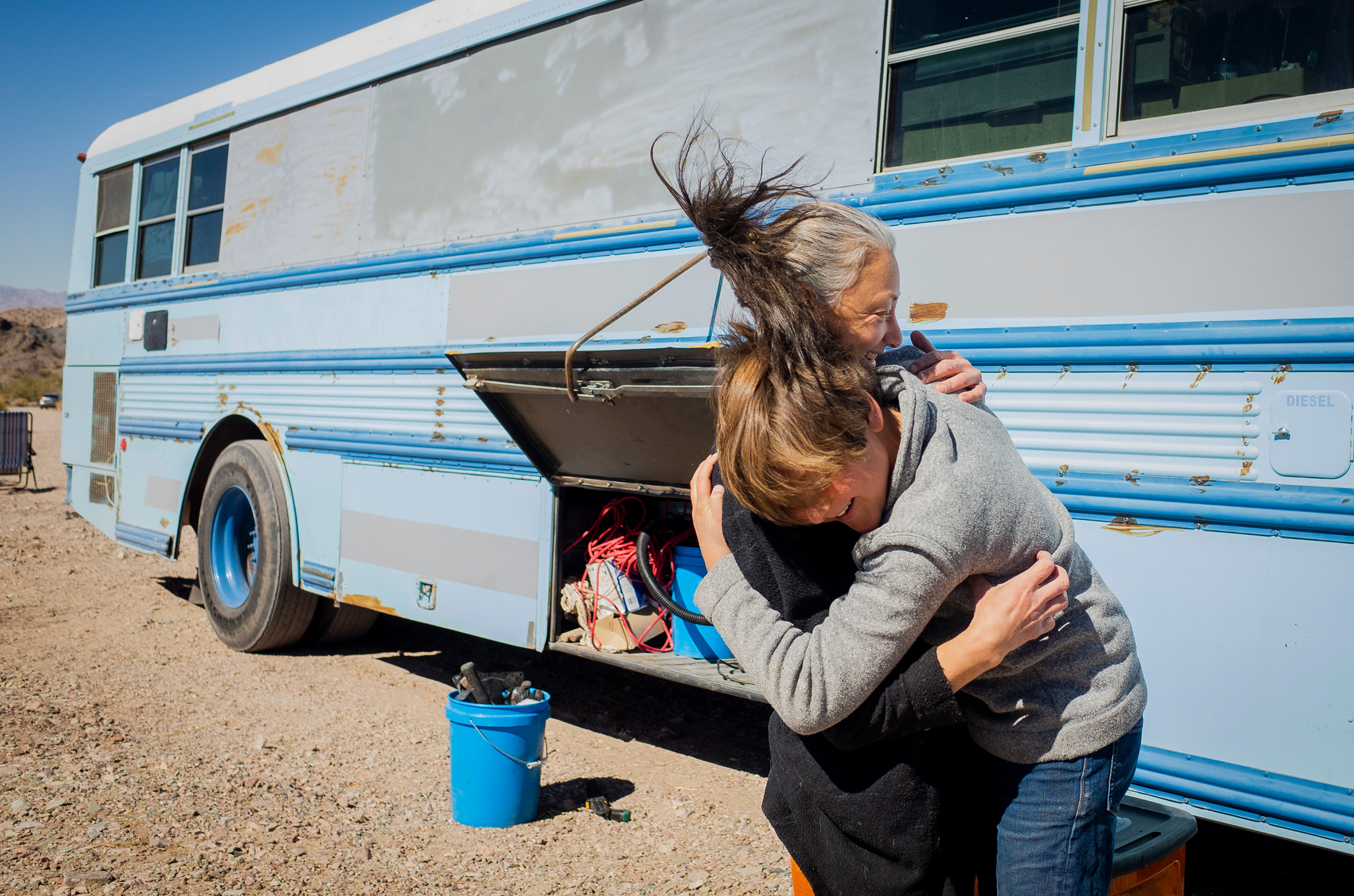 """Paula and Max embrace after working on construction projects for the bus on Feb. 20. They're careful to clean up after themselves after renovations. Paula says that, in her experience, people living out of skoolies or vans are usually the most respectful towards the land itself. """"The people who stay and do full time living, they would like to keep the privilege,"""" she explains. """"[We're] usually the ones that go out and clean up after all of the people that leave stuff behind."""""""