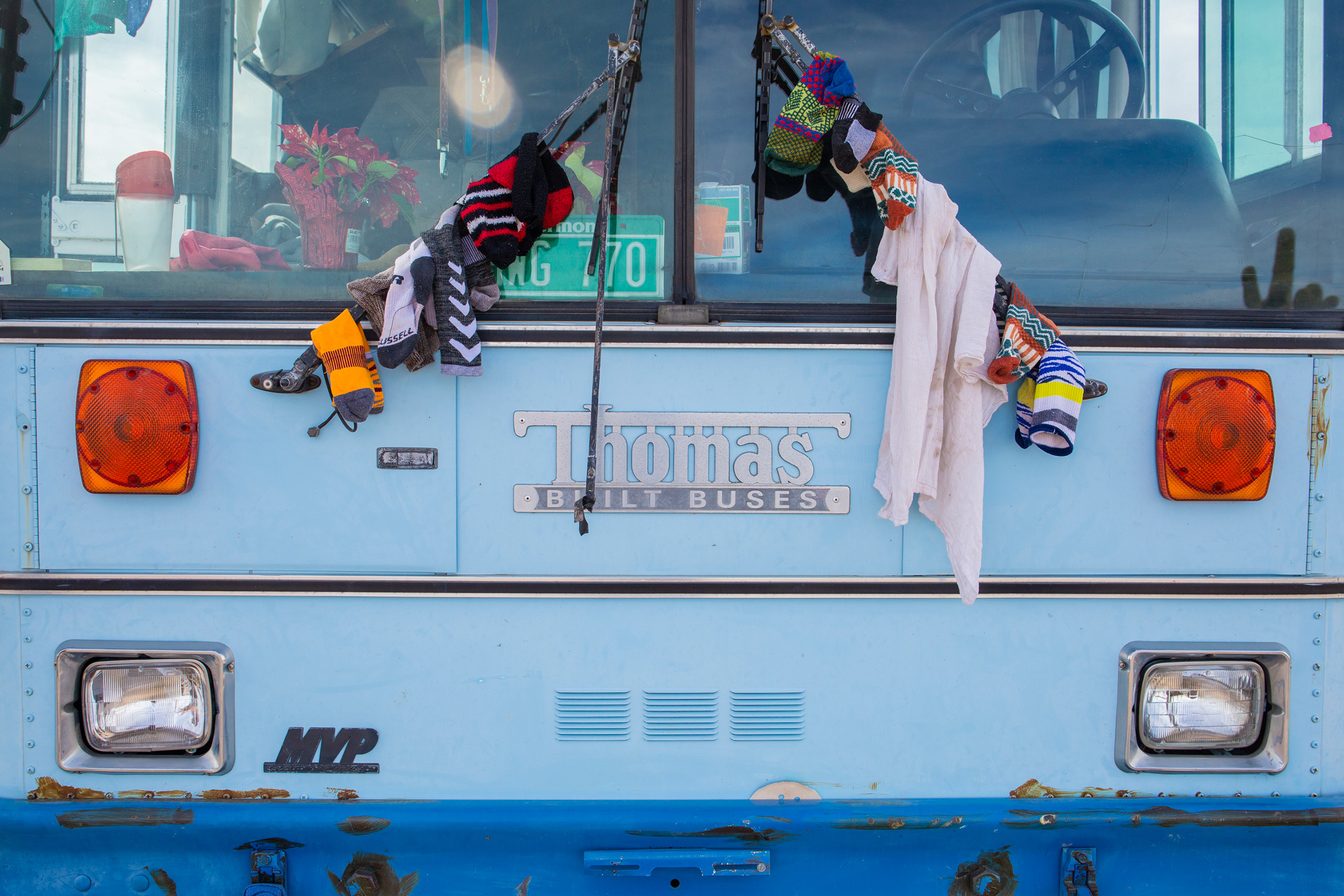 Paula and Max hang laundry on the bus to dry.