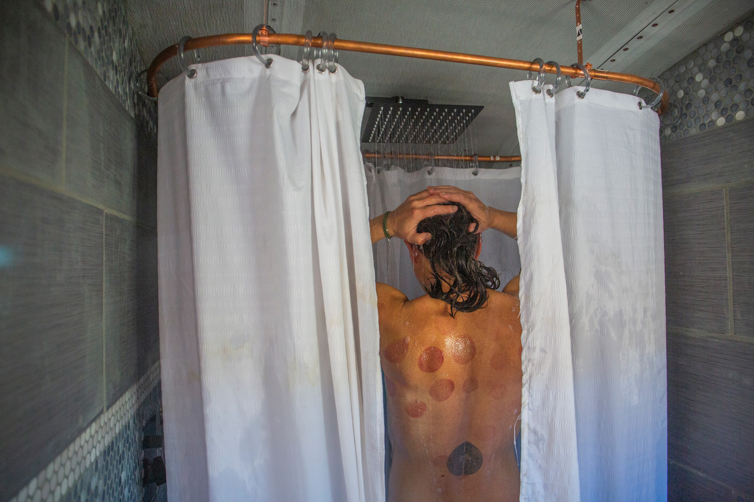 Paula showers in her handmade bathroom on the school bus, which includes a compost toilet and bathtub made from a metal trough. She suffered a major back injury years ago, and the bruising on her back is from 'cupping,' a form of alternative medicine often used to treat muscle pain, which she lets Max practice on her when she is stressed.