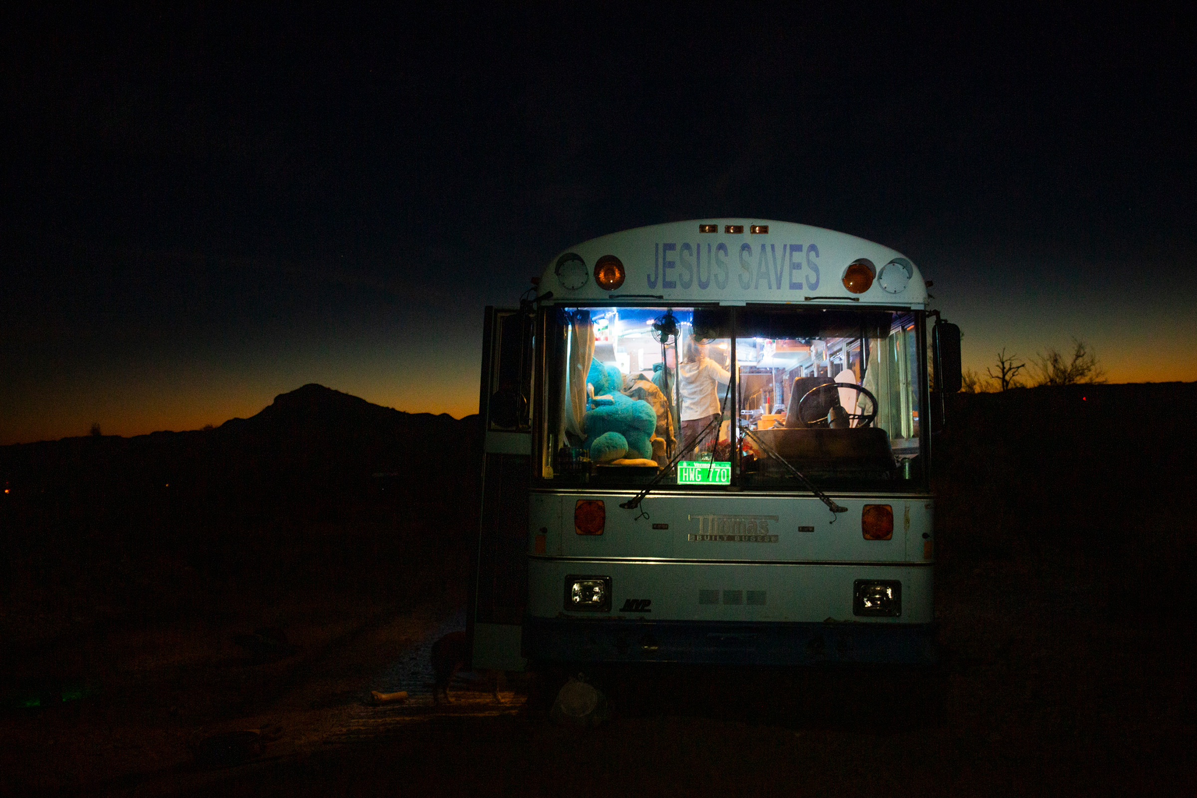 Paula and Max's 'Jesus Saves' bus provides warmth on cold desert nights outside Lake Havasu City, Az., on Feb. 23. Paula was raised Jewish and does not identify as Christian; she found the retired Baptist school bus in San Diego last year and it fit within her budget.