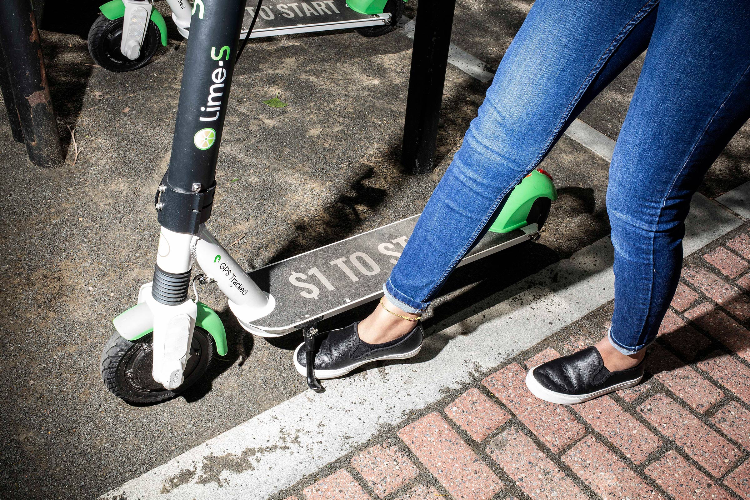 A woman prepares to ride a Lime scooter in Hoboken, N.J. on May 24, 2019.