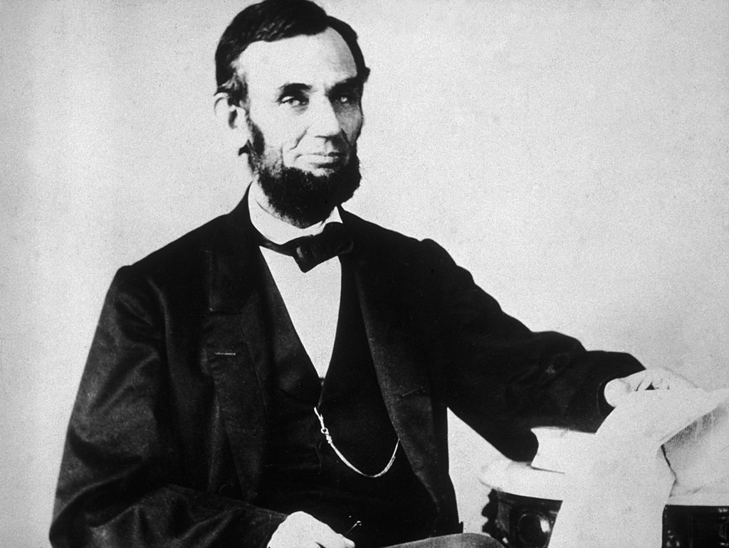 The 16th American president, Abraham Lincoln (1809 - 1865), sitting and leafing through documents, Washington, D.C.