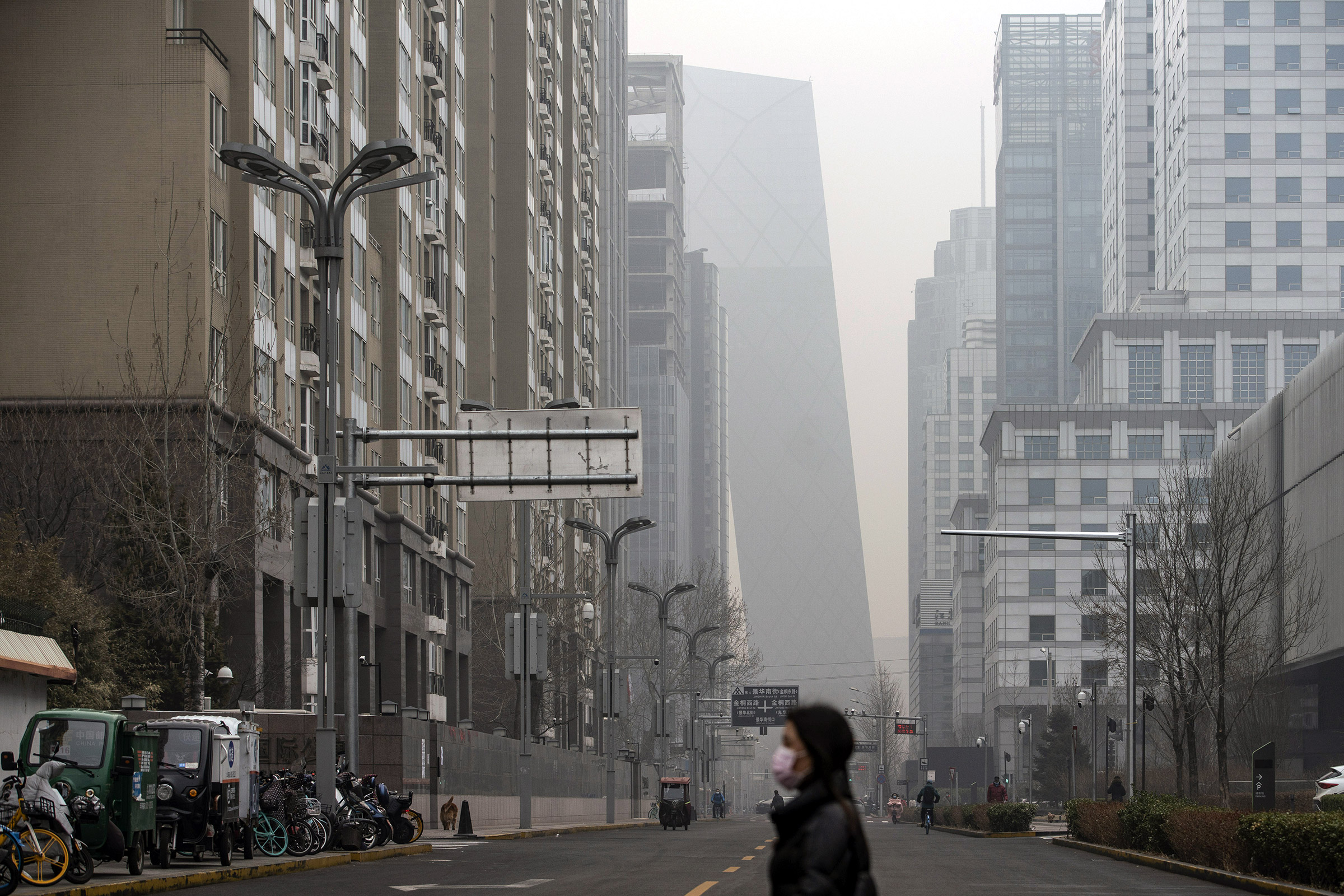 A pedestrian walks in Beijing, shrouded in smog, on March 5, 2021.