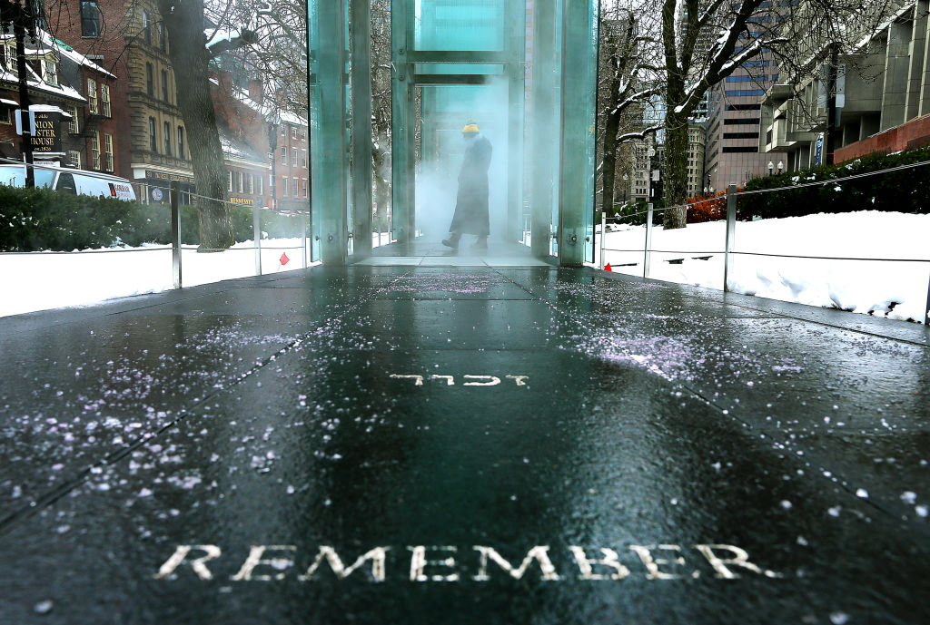 A person pauses to look at the inscriptions, representing the six million Jews killed in the Holocaust, inside the glass walls at the New England Holocaust Memorial in Boston on Jan. 27, 2021