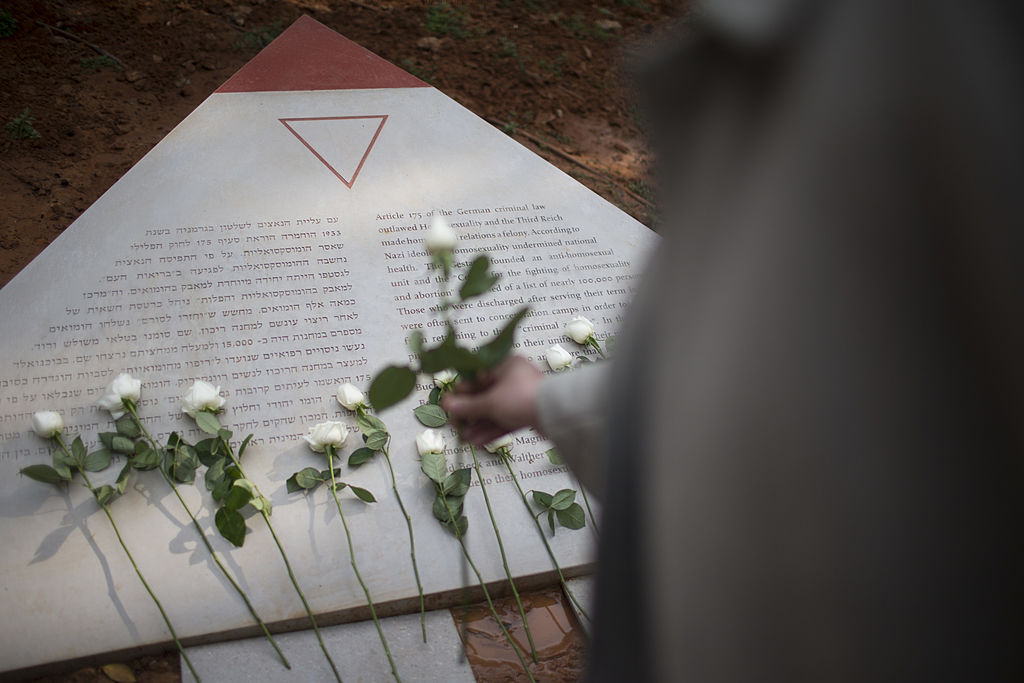 A man lays a white rose at a memorial inaugurated to lesbian, gay, bisexual and transgender victims of the Holocaust on Jan. 10, 2014 in Tel Aviv, Israel.