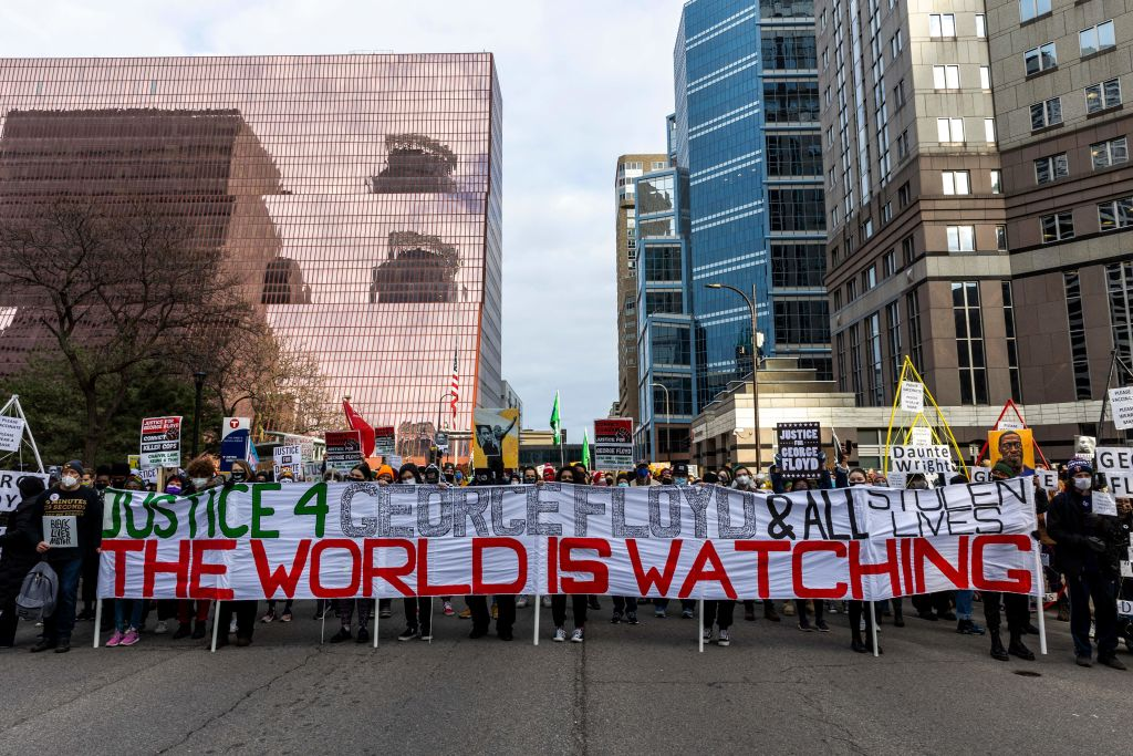 Protesters hold a banner during a demonstration outside the Hennepin County Government Center in Minneapolis on April 19, 2021.