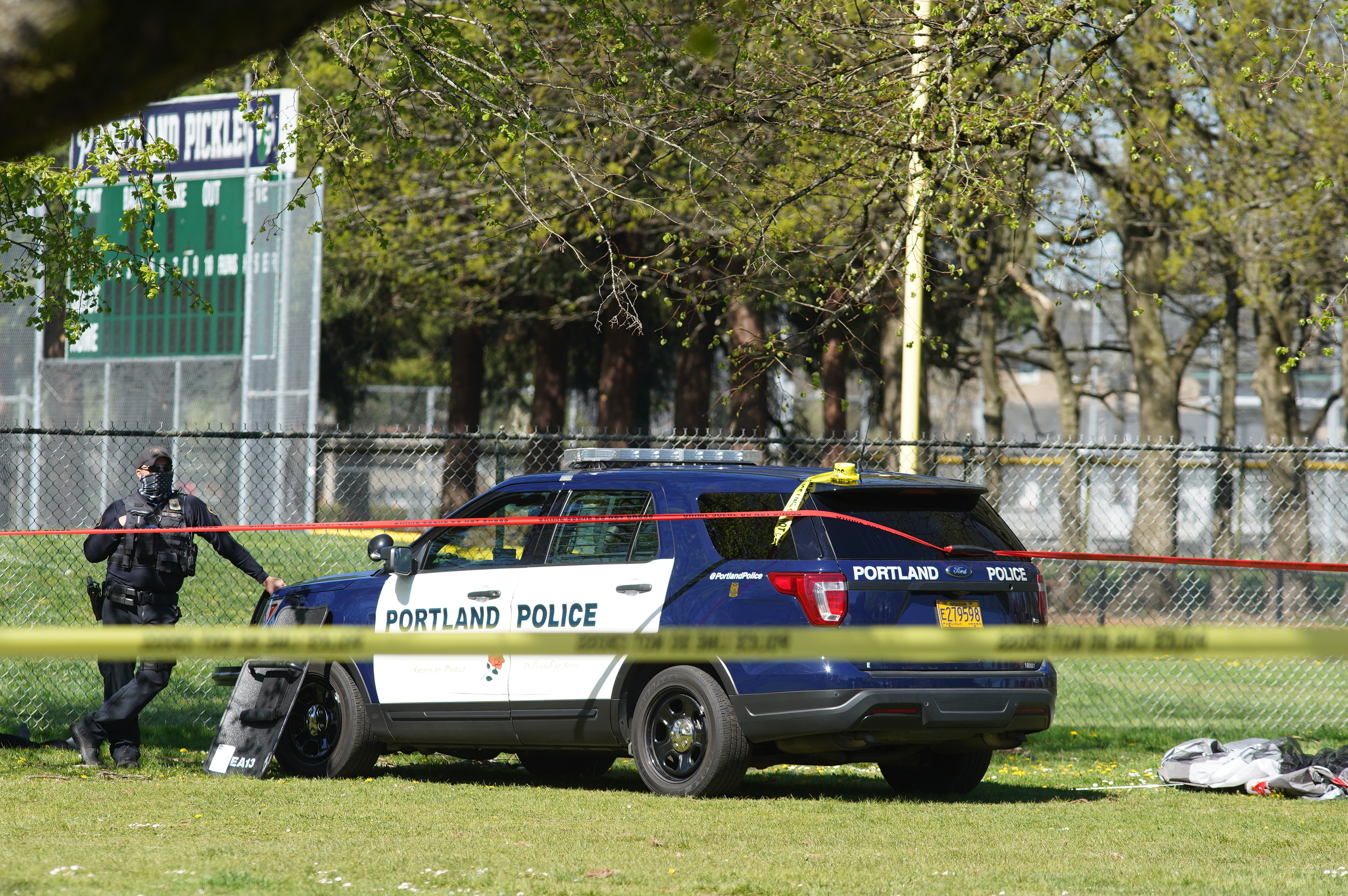 A Portland Police officer stand by following a police involved shooting of a man at Lents Park, on, April 16, 2021.