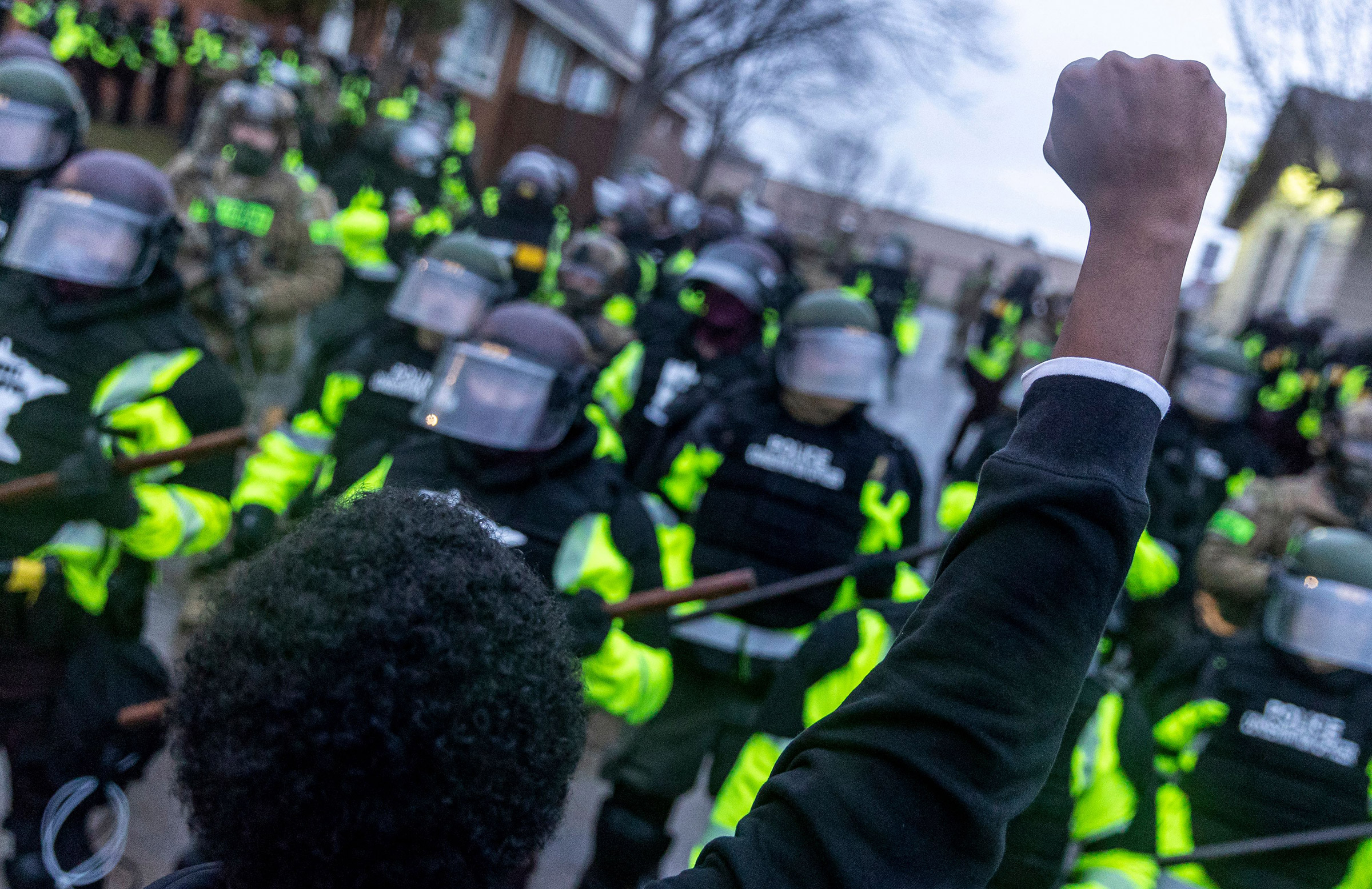 A man raises his fist as he faces the Minnesota State Troopers standing guard outside the Brooklyn Center Police Station after a police officer shot and killed 20-year-old Daunte Wright during a traffic stop in Brooklyn Center, Minneapolis, Minnesota on April 12, 2021.