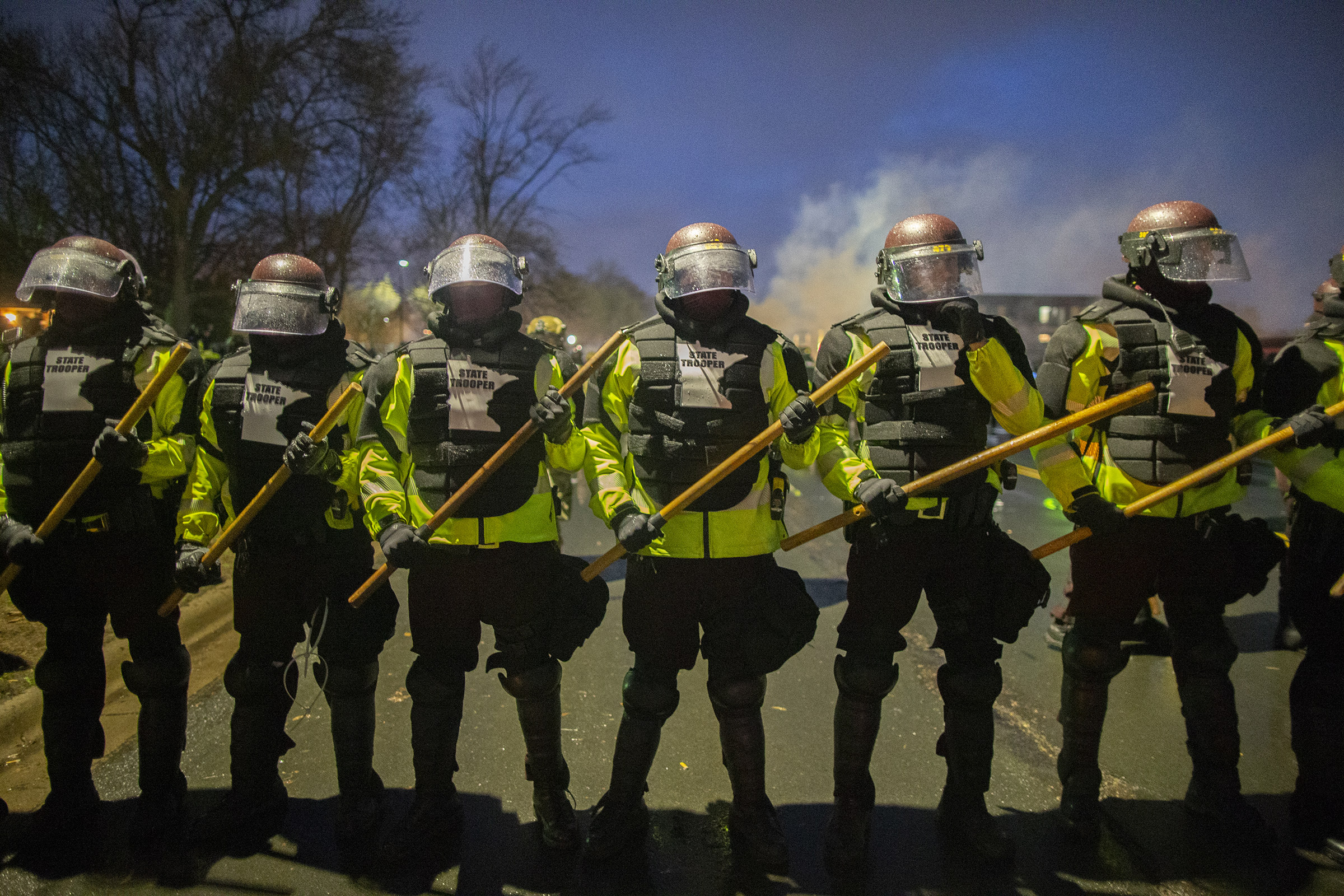 Tear gas rises from behind a line of Minnesota State Troopers as they block the road from anyone going back towards the Brooklyn Center police station where people protesting the police killing of Daunte Wright in Brooklyn Center, Minnesota, U.S., on April 13, 2021.