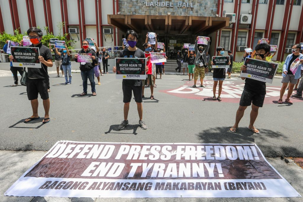 People from Bagong Alyansang Makabayan (Bayan) take part in a protest against the Philippine government-ordered shutdown of broadcaster ABS-CBN while observing social distancing outside the College of Mass Communication at the University of the Philippines in Manila on May 8, 2020.