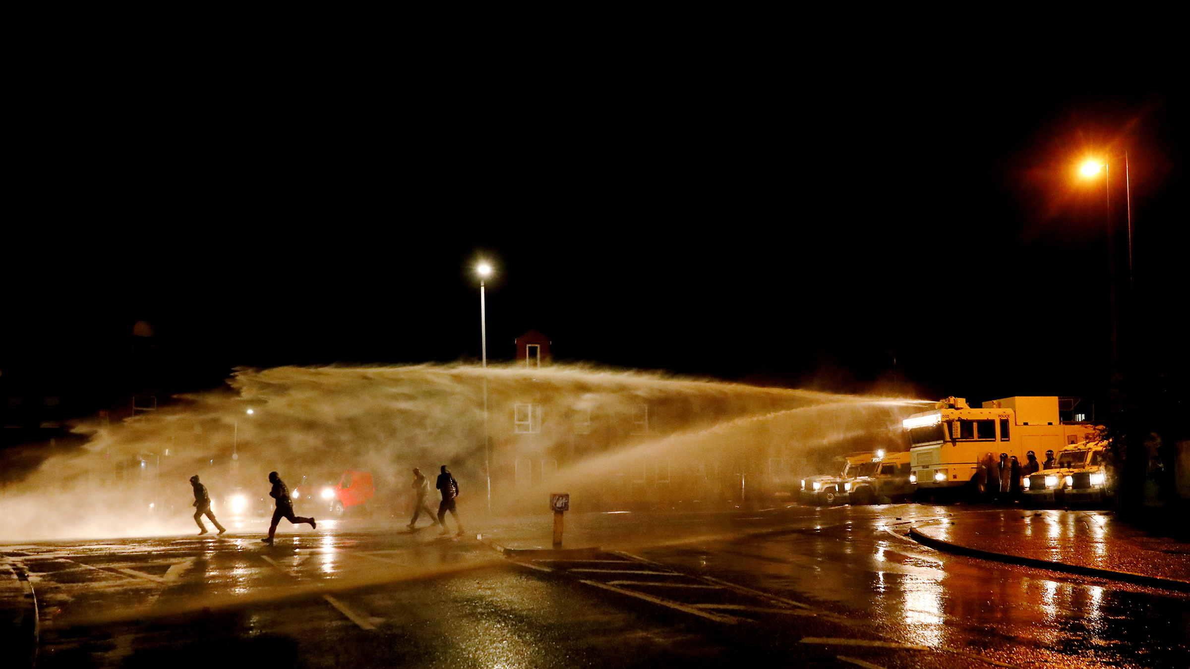 Rioters react as the police uses a water cannon on Springfield Road as protests continue in Belfast on April 8