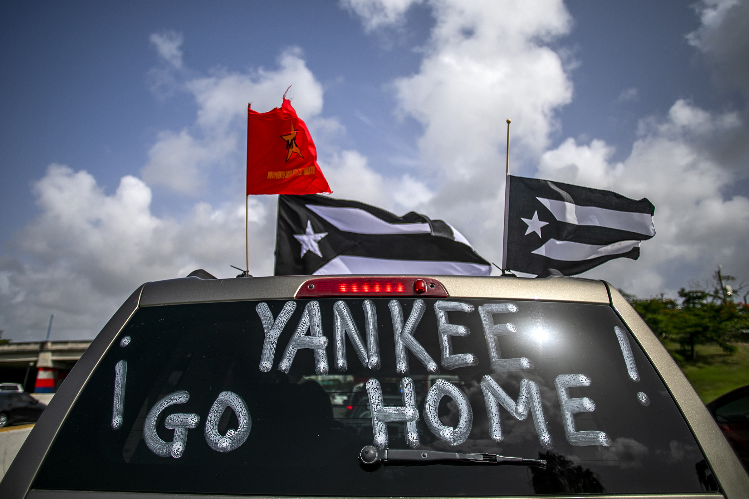 Yankee Go Home  is displayed on a vehicle during a protest against U.S. mainland tourist arriving from coronavirus hot zones outside Luis Munoz Airport in San Juan, Puerto Rico, on July 25, 2020.