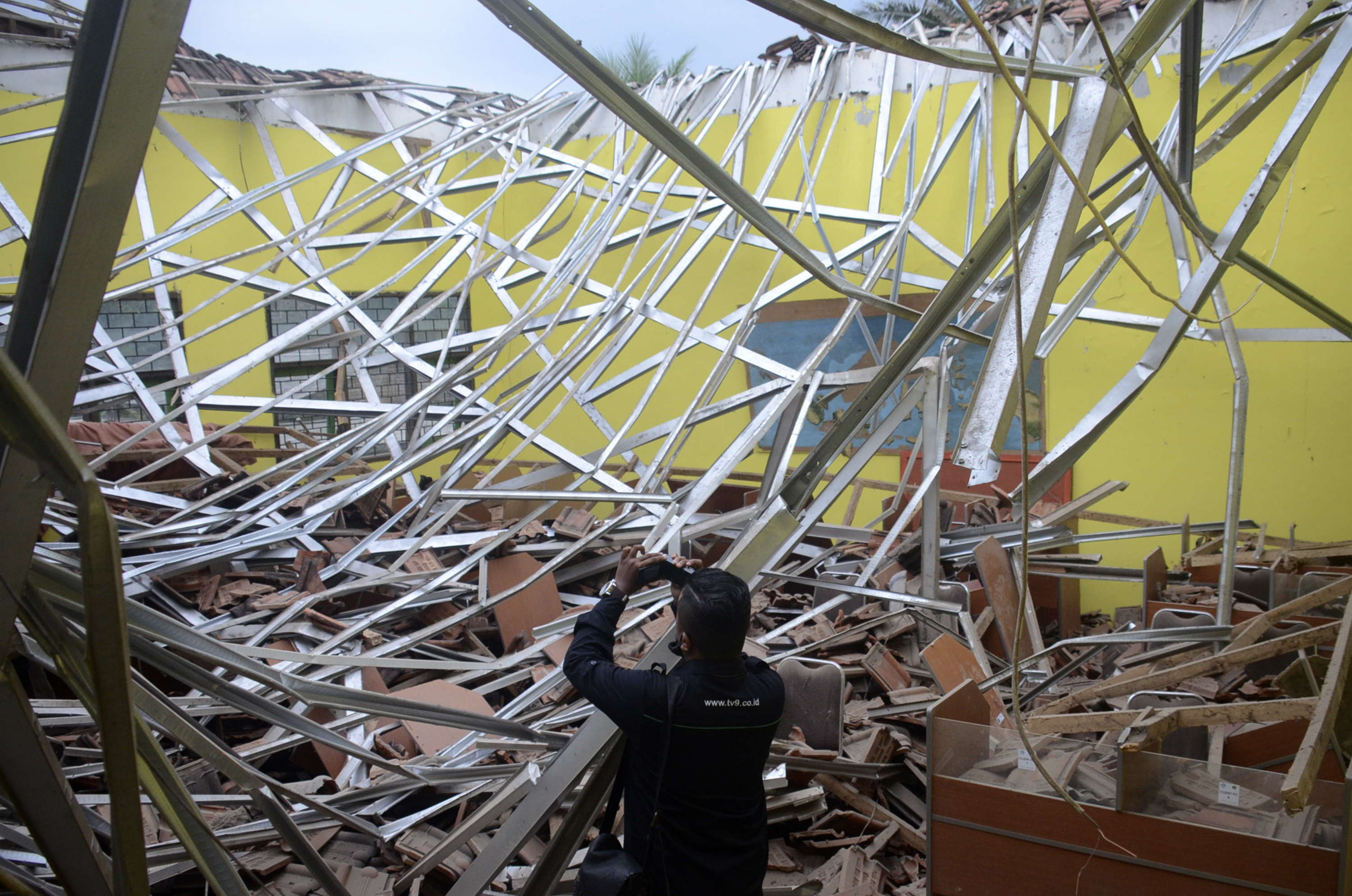 A local journalist films the damage to a class room at a school following an earthquake in Malang, East Java, Indonesia, on April 10, 2021.