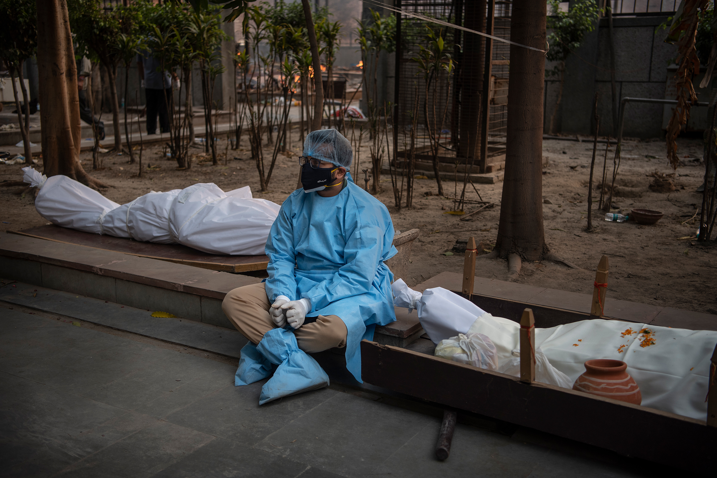 A man waits for his family's turn to cremate the body of their loved one, who died from COVID-19, in New Delhi on April 27.