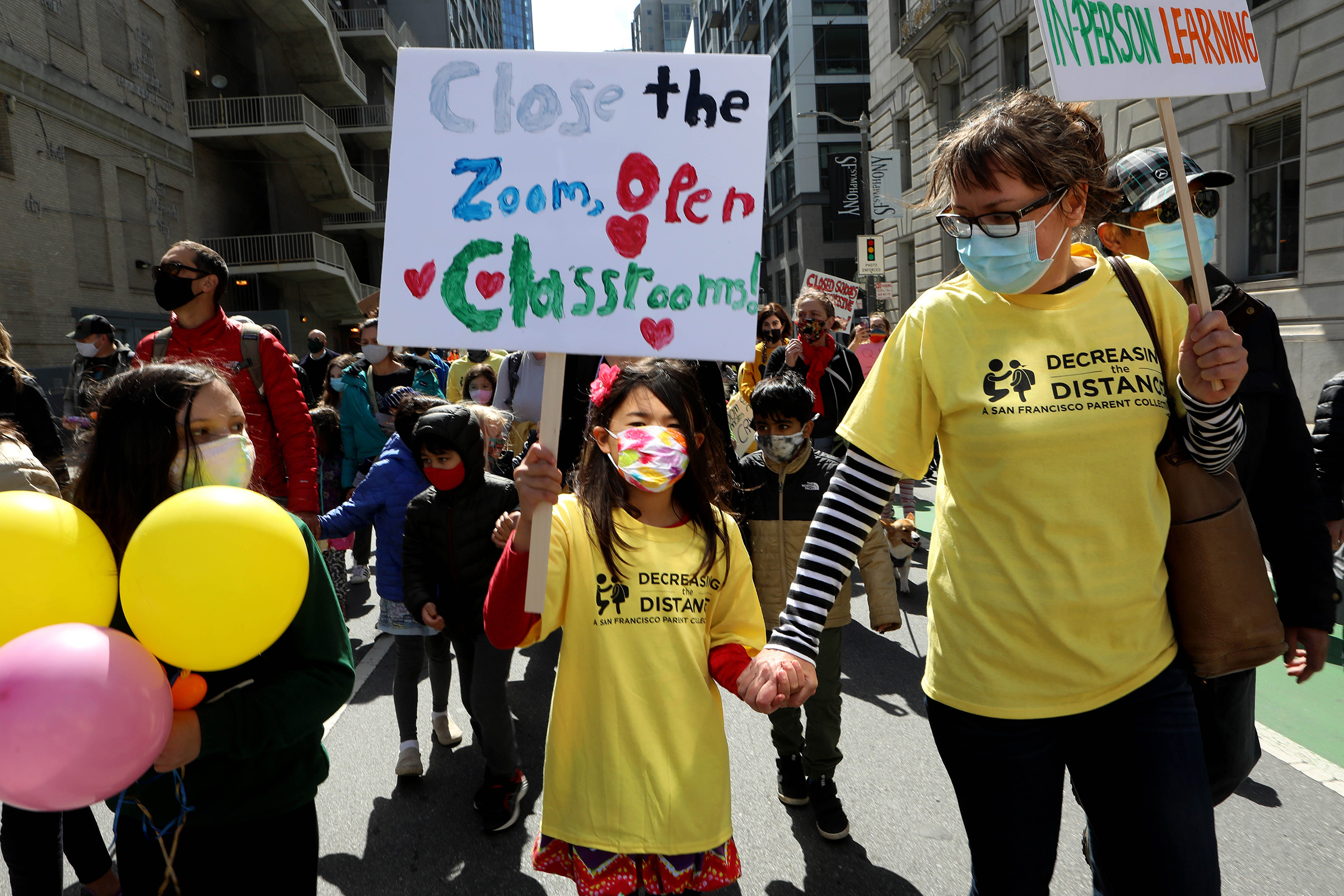 Kristina Leng, 9, marches to the Civic Center with her mother Monika Leng, and father Rodney Leng during the Families Rally to Demand Schools Fully Reopen event  in San Francisco, on March 13, 2021.