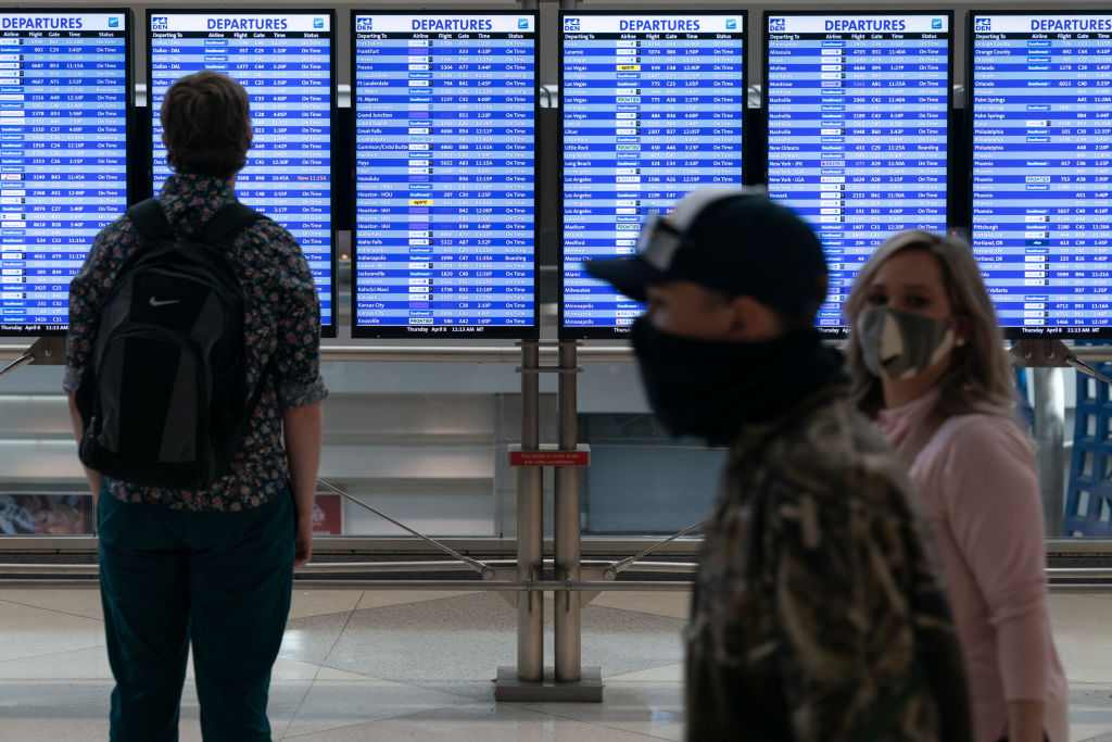 Passengers wearing protective masks walk past a departures board at Denver International Airport in Denver, Colo., on April 8, 2021.