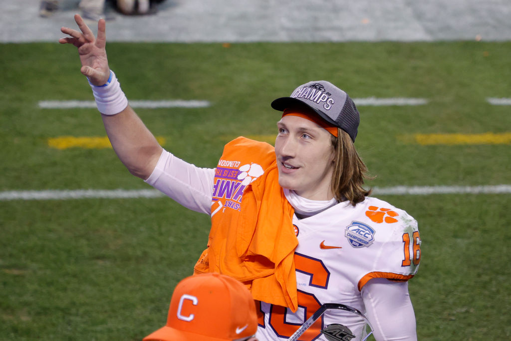 Quarterback Trevor Lawrence of the Clemson Tigers acknowledges fans as he walks off the field after defeating the Notre Dame Fighting Irish 34-10 in the ACC Championship game at Bank of America Stadium on December 19, 2020 in Charlotte, N.C.