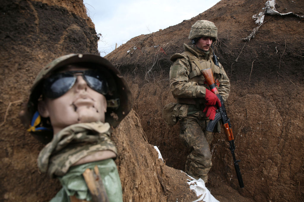 An Ukrainian serviceman walks in a trench by a sort of mannequin as he stands at his post on the frontline with Russia backed separatists near the town of Zolote, in the Lugansk region on April 8, 2021. - Ukrainian President Volodymyr Zelensky was travelling to the country's eastern frontline on April 8, 2021, after a surge in clashes with separatist forces and a spike in tensions with Moscow. Fighting between the Ukrainian army and separatists has intensified in recent weeks, raising fears of a major escalation in the long-running conflict over the mainly Russian-speaking Donbas region. (Photo by STR / AFP) (Photo by STR/AFP via Getty Images)