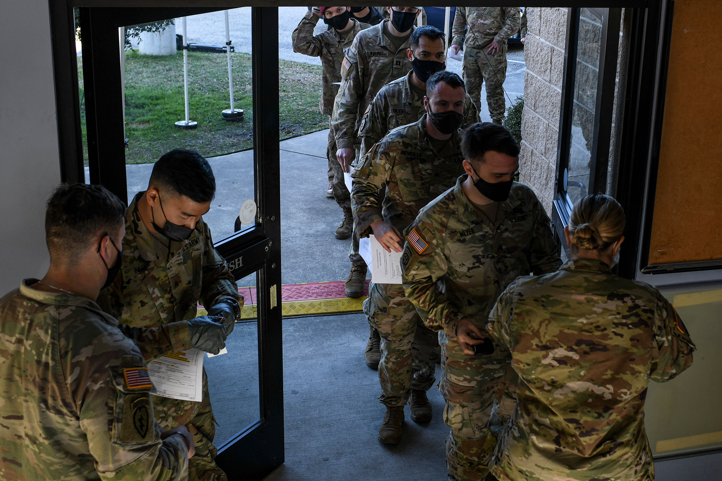 Soldiers line up for a medical screening before receiving the coronavirus vaccine at Fort Bragg in North Carolina, Feb. 24, 2021.